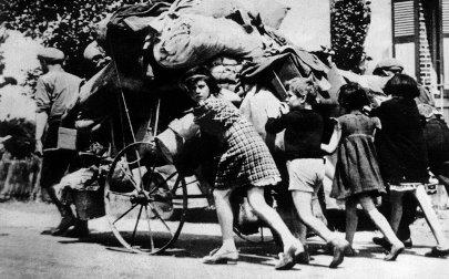 Sur les routes de l'exode. Les civils quittent leur maison avec leurs maigres bien sur des moyens de fortune.